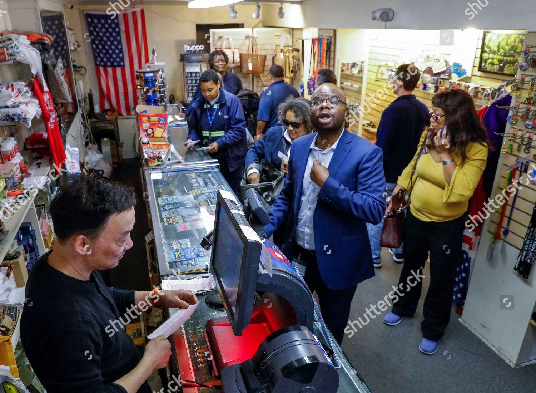 Customers wait purchase Mega Millions lottery tickets