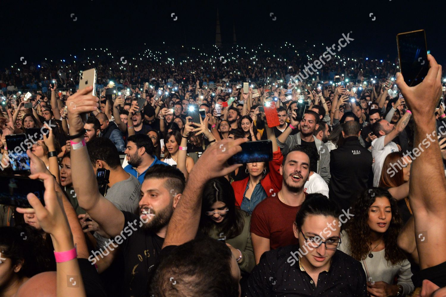 People rise their illuminated cell phones during Editorial