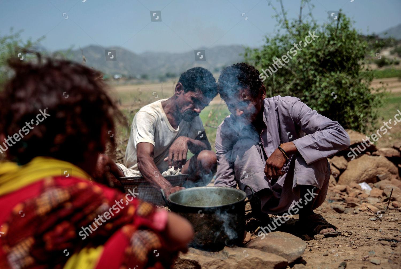 Men cook Halas their children climbing vine Editorial Stock