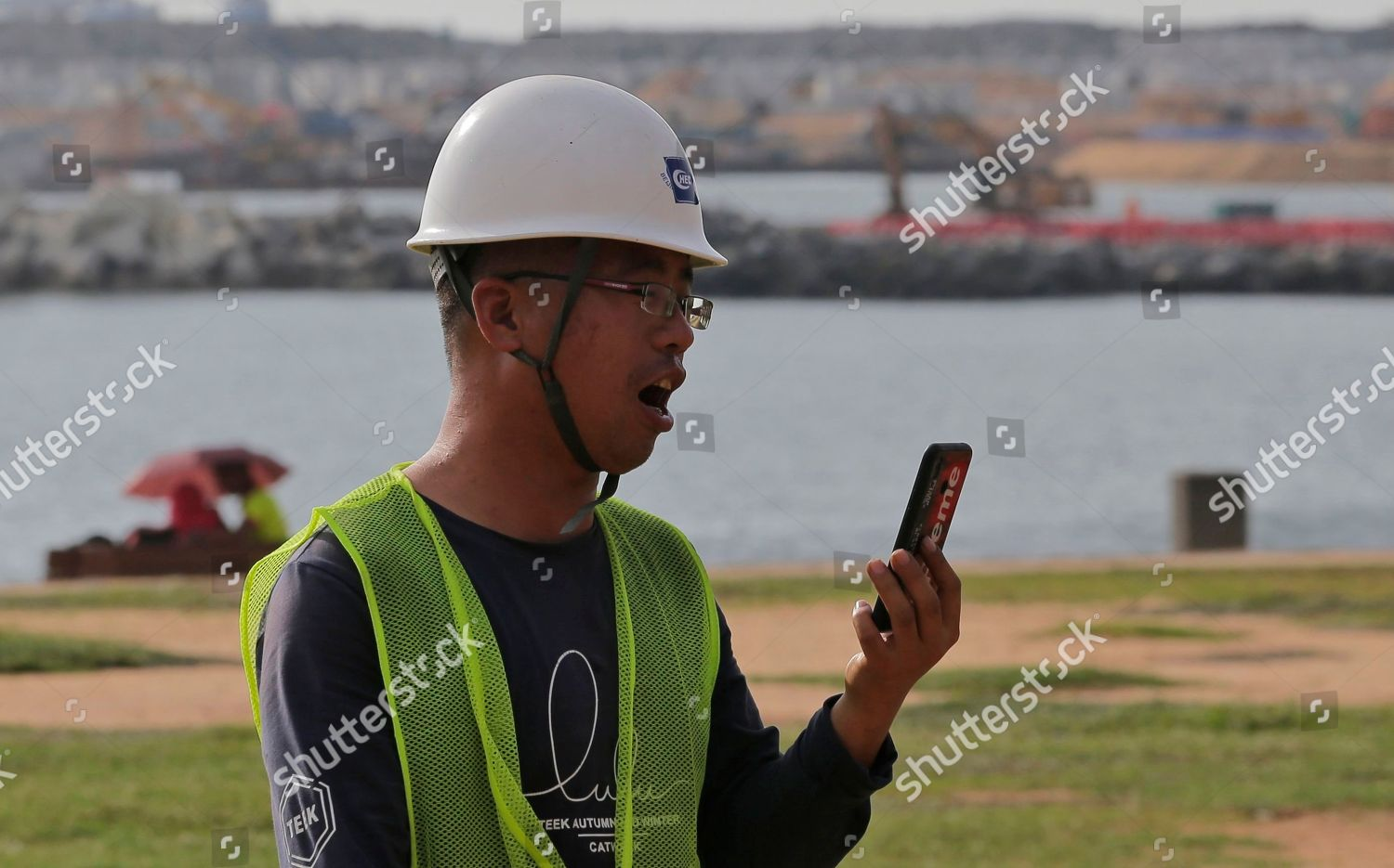 Chinese construction worker speaks on his mobile Editorial
