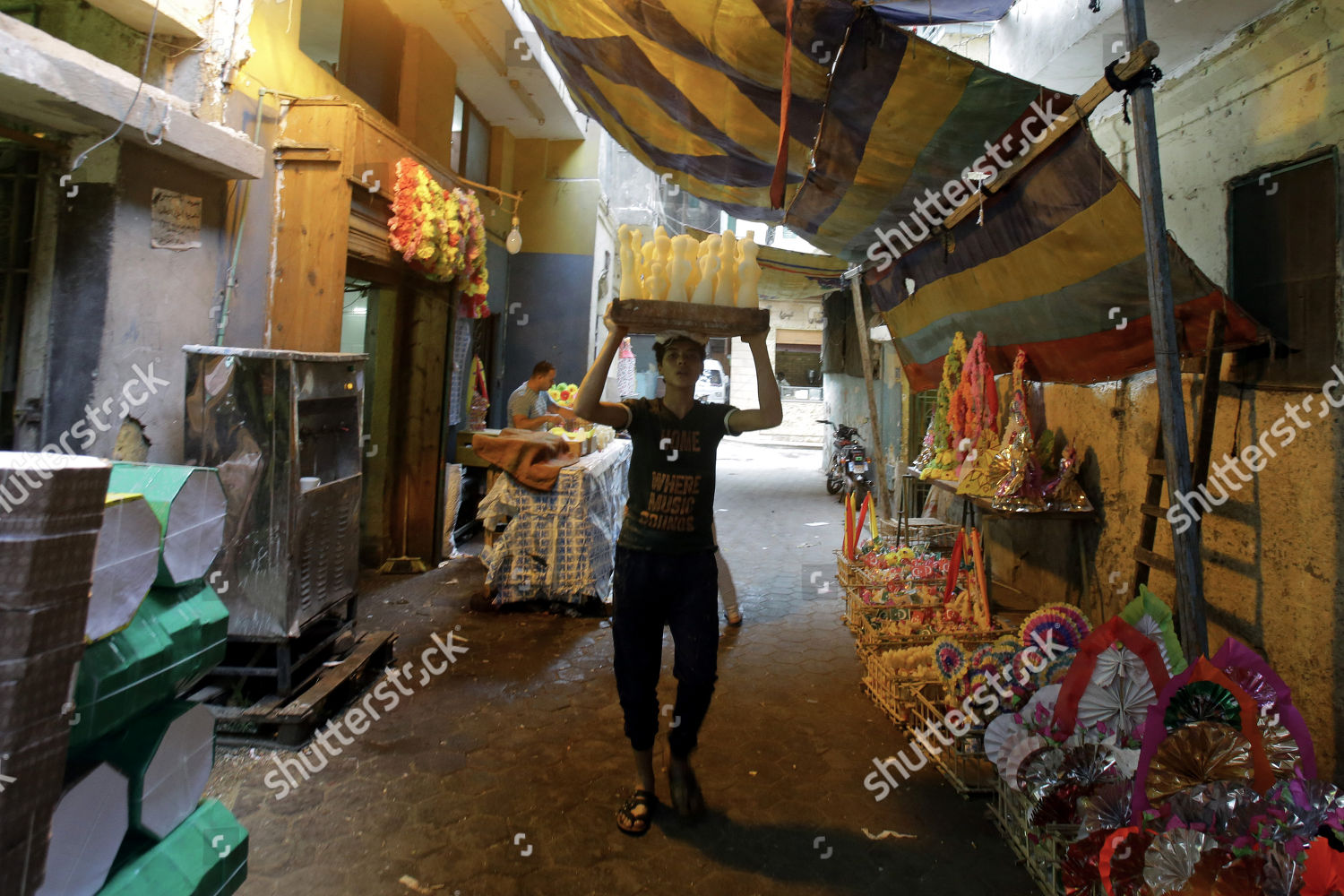 Egyptian factory worker carries candy dolls preparation
