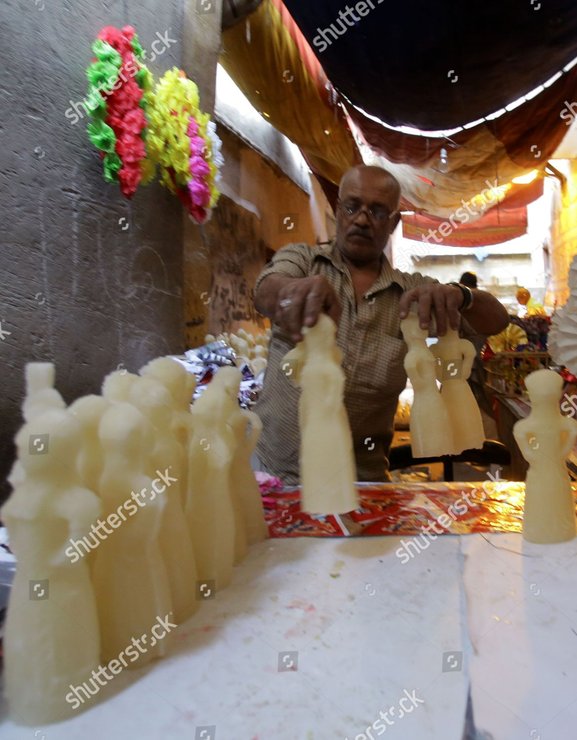 Egyptian factory worker organizes candy dolls preparation