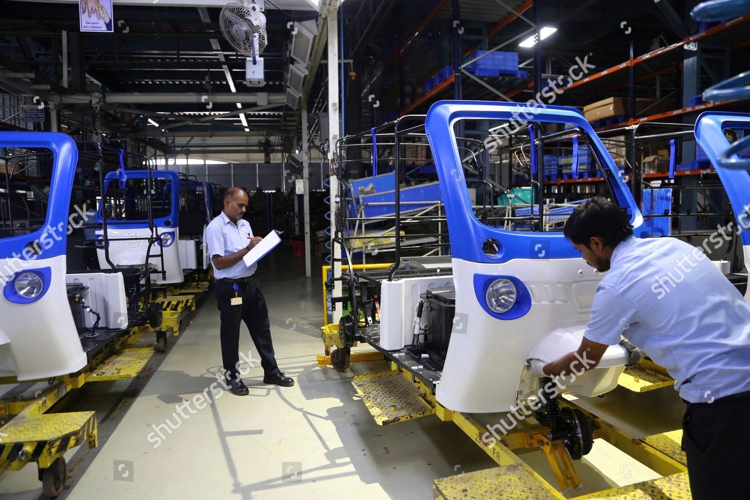 Indian workers perform check on threewheeler electric