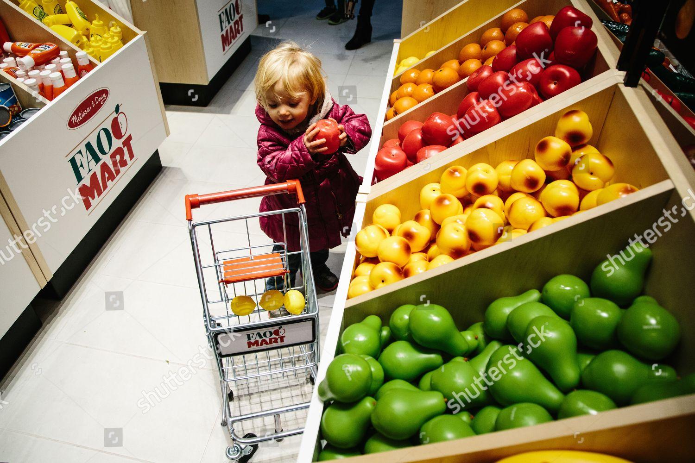 little girl plays mart section FAO Scharwz Editorial Stock