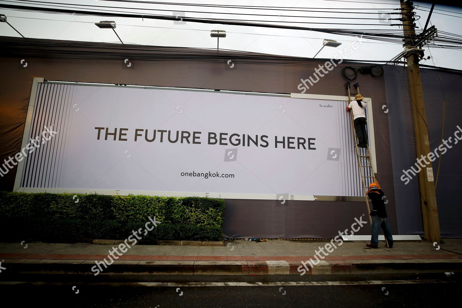 Workers intall large billboard outside construction site Editorial