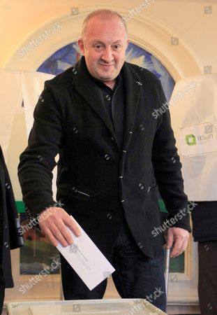 Georgian President Giorgi Margvelashvili casts his ballot for the presidential election in Tbilisi, Georgia, . Two of Georgia's former foreign ministers are facing off against each other Wednesday in a tight runoff that will mark the last time Georgians elect their head of state by popular vote