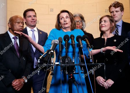 Nancy Pelosi, Kathy Castor, Eric Swalwell, Joyce Beatty, John Lewis, Joe Kennedy. House Minority Leader Nancy Pelosi, D-Calif., joined by from left, Rep. John Lewis, D-Ga., Rep. Eric Swalwell, D-Calif., Rep. Joyce Beatty, D-Ohio., Rep. Kathy Castor, D-Fla., and Rep. Joe Kennedy, D-Mass., gestures as she speaks to media at Longworth House Office Building on Capitol Hill in Washington, to announce her nomination by House Democrats to lead them in the new Congress