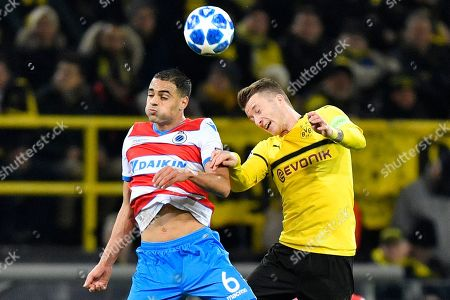Brugge midfielder Sofyan Amrabat, left, and Dortmund's Marco Reus challenge for the ball during the Champions League group A soccer match between Borussia Dortmund and Club Brugge in Dortmund, Germany