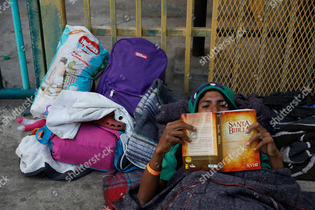 "Luis Rene Reyes Garcia, 28, of Guatemala, reads a donated bible as he rests on the street outside of a sports complex where more than 5,000 Central Americans are sheltering, in Tijuana, Mexico, . ""At home I drank a lot, but now I've quit,"" said Reyes. ""I am getting closer to god."" Reyes, who worked in banana packing in Guatemala, said he joined the caravan to find a way to earn money to support his daughter back home"