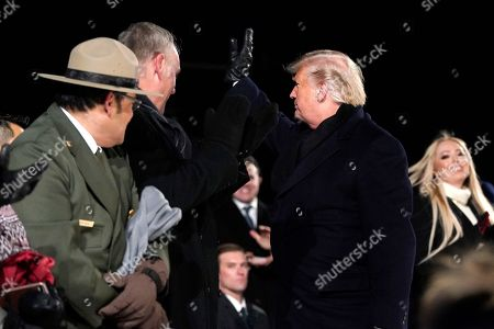 Donald Trump, Melania Trump. President Donald Trump waves with Interior Secretary Ryan Zinke during the National Christmas Tree lighting ceremony at the Ellipse near the White House in Washington