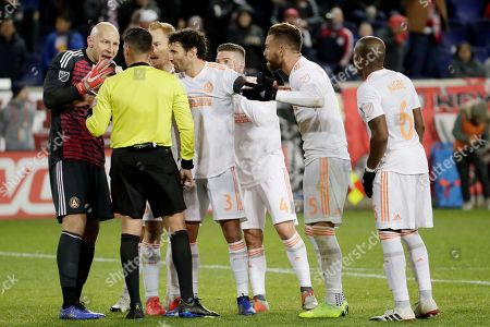 Atlanta United goalkeeper Brad Guzan, left, and teammates talk to referee Jair Marrufo after the Red Bulls scored a goal during the second half of the second leg of the MLS soccer Eastern Conference championship, in Harrison, N.J. The goal was annulled because Red Bulls' Aaron Long made contact with Guzan on the play. The Red Bulls won 1-0, but Atlanta United won 3-1 on aggregate
