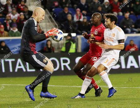 Atlanta United goalkeeper Brad Guzan, left, comes out to make a save while New York Red Bulls forward Bradley Wright-Phillips and Atlanta United defender Michael Parkhurst race toward the ball during the second leg of an MLS Eastern Conference Championship soccer match, in Harrison, N.J