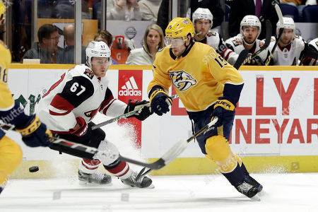 Nashville Predators right wing Craig Smith (15) and Arizona Coyotes left wing Lawson Crouse (67) chase the puck in the second period of an NHL hockey game, in Nashville, Tenn