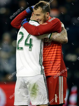 Jeff Attinella, Liam Ridgewell. Portland Timbers goalkeeper Jeff Attinella (1) celebrates with defender Liam Ridgewell (24) following the second leg of the MLS soccer Western Conference championship against Sporting Kansas City in Kansas City, Kan