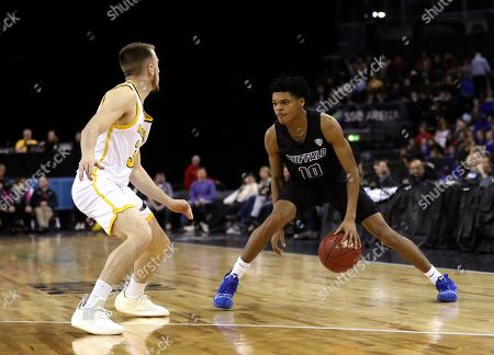 Buffalo's Ronaldo Segu, right, against Milwaukee's Te Jon Lucas during the first half of an NCAA college basketball game between the Buffalo Bulls and the Milwaukee Panthers, in Belfast