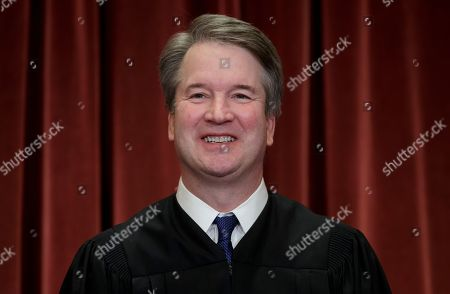 Associate Justice Brett M. Kavanaugh, appointed by President Donald Trump, sits with fellow Supreme Court justices for a group portrait at the Supreme Court Building in Washington