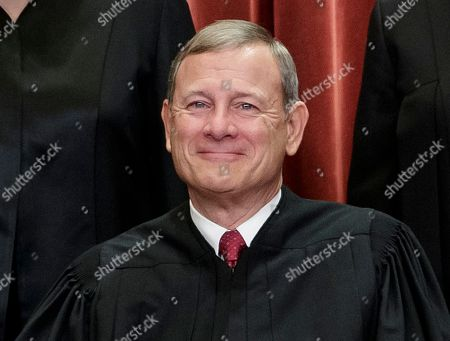Chief Justice of the United States, John G. Roberts, nominated by President George W. Bush, sits with fellow Supreme Court justices for a group portrait at the Supreme Court Building in Washington