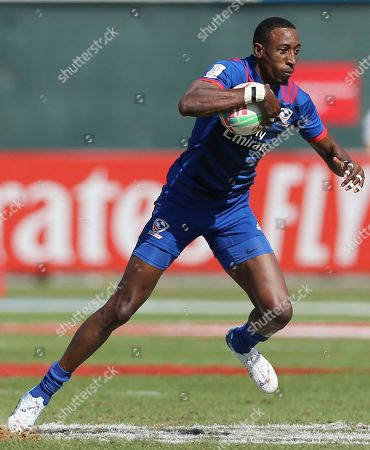 America's Perry Baker runs with ball against Fiji in a quarterfinal match of the Emirates Airline Rugby Sevens in Dubai, the United Arab Emirates