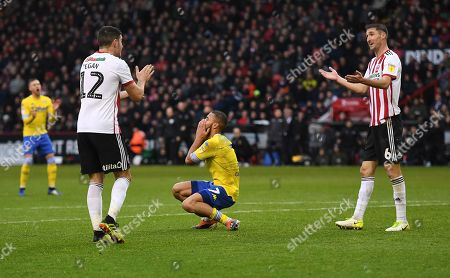 Kemar Roofe of Leeds United rues a missed chance as John Egan and Chris Basham of Sheffield United have their own chat