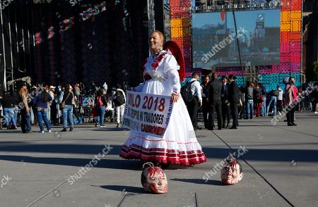 A woman stands next to two masks depicting former President Felipe Calderon, left, and outgoing President Enrique Pena Nieto, as she arrives to the Zocalo to take part in the inaugural festivities, in Mexico City, . Mexicans are getting more than just a new president Saturday. The inauguration of President-elect Andres Manuel Lopez Obrador will mark a turning point in one of the world's most radical experiments in opening markets and privatization