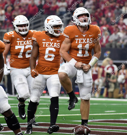 Stock Image of Texas quarterback Sam Ehlinger (11) celebrates after scoring on a touchdown run as Devin Duvernay (6) and Elijah Rodriguez (72) look on during the first half of the Big 12 Conference championship NCAA college football game against Oklahoma, in Arlington, Texas