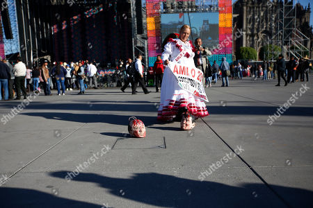A woman kicks a mask depicting outgoing President Enrique Pena Nieto, as she arrives to the Zocalo to take part in the inaugural festivities, in Mexico City, . Mexicans are getting more than just a new president Saturday. The inauguration of President-elect Andres Manuel Lopez Obrador will mark a turning point in one of the world's most radical experiments in opening markets and privatization. The other mask depicts former President Felipe Calderon