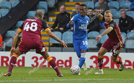 Stock Picture of Siriki Dembele of Peterborough United takes on Karl Henry and David Ball of Bradford City