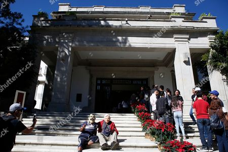 Enedino Camarillo, who wears a mask representing former Mexican President Vicente Fox, and Luis Duque wearing a mask depicting Andres Manuel Lopez Obrador, sit on the front steps of the Casa Miguel Aleman, the presidential residence know as Los Pinos, in Mexico City, . A few hundred people showed up for the opening of the compound, known as Los Pinos; it was closed for so long that many people don't know where the entrances are