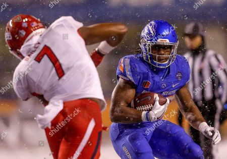 Boise State running back Alexander Mattison carries the ball as Fresno State linebacker James Bailey (7) closes in during the second half of an NCAA college football game for the Mountain West championship, in Boise, Idaho. Fresno State won 19-16