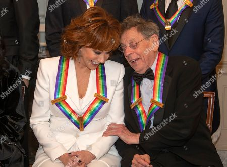 Reba McEntire, left, and Philip Glass two of the recipients of the 41st Annual Kennedy Center Honors, converse as they pose for a group photo following a dinner