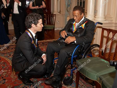 Thomas Kail, left, and Wayne Shorter, right, two of the recipients of the 41st Annual Kennedy Center Honors, converse after posing for a group photo following a dinner