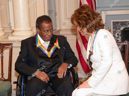Wayne Shorter, left and Reba McEntire, right, two of the recipients of the 41st Annual Kennedy Center Honors, converse prior to posing for a group photo following a dinner