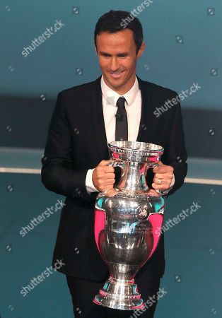 Former Portuguese soccer player and European champion Ricardo Carvalho brings the trophy to the stage during the UEFA Euro 2020 European soccer championship qualifying draw at the Convention Centre in Dublin, Ireland