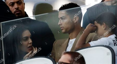 Juventus forward Cristiano Ronaldo, center, is flanked by his girlfriend Georgina, left, and his son Cristiano Jr., as he sits in the stands during a Champions League group H soccer match between Juventus and Young Boys, at the Allianz stadium in Turin, Italy, on