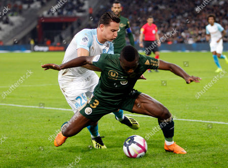 Marseille's Florian Thauvin, left, with Reims' Ghislain Konan, during the League One soccer match between Marseille and Reims at the Velodrome stadium, in Marseille, southern France