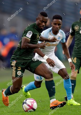 Reims' Ghislain Konan, left, challenges for the ball with Marseille's Bouna Sarr, during the League One soccer match between Marseille and Reims at the Velodrome stadium, in Marseille, southern France