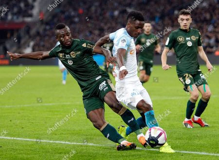Marseille's Bouna Sarr, right, challenges for the ball with Reims' Ghislain Konan, during the League One soccer match between Marseille and Reims at the Velodrome stadium, in Marseille, southern France