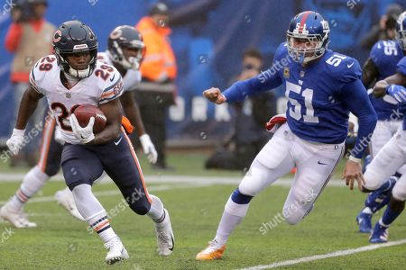 Stock Image of Chicago Bears' Tarik Cohen, left, returns a punt as New York Giants' Zak DeOssie (51) chases after him during the first half of an NFL football game, in East Rutherford, N.J
