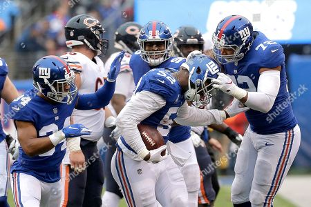 Stock Photo of New York Giants outside linebacker Alec Ogletree, center, celebrates his of Chicago Bears quarterback Chase Daniel, not pictured, with teammates defensive back Grant Haley (34), outside linebacker Kareem Martin (96) and defensive end Kerry Wynn (72) during the first half of an NFL football game, in East Rutherford, N.J