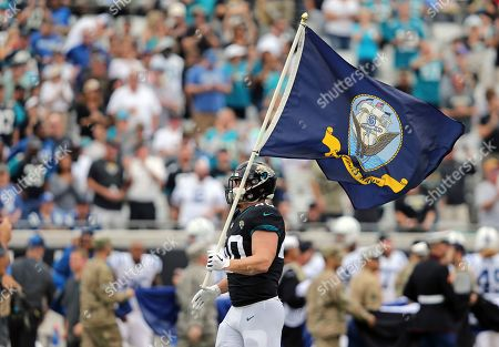 Stock Picture of Jacksonville Jaguars fullback Tommy Bohanon brings out a U.S. Navy flag on the field during the Salute to Service activities before an NFL football game against the Indianapolis Colts, in Jacksonville, Fla