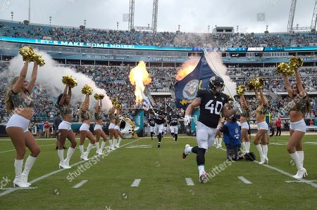 Jacksonville Jaguars fullback Tommy Bohanon (40) carries a U.S. Military flag onto the field as part of Salute to Service activities before an NFL football game against the Indianapolis Colts, in Jacksonville, Fla