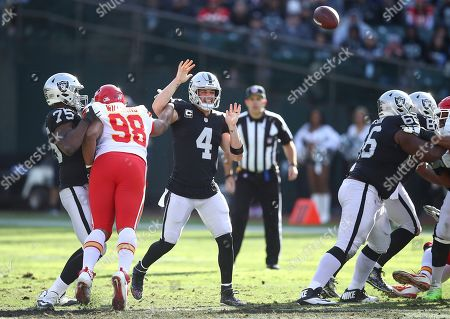 Oakland Raiders quarterback Derek Carr (4) is hit while throwing by Kansas City Chiefs nose tackle Xavier Williams (98) during the first half of an NFL football game in Oakland, Calif