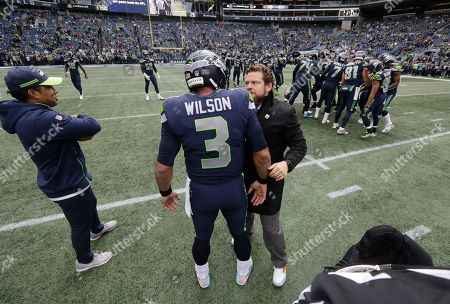 Seattle Seahawks Seattle Seahawks general manager John Schneider, center, talks with quarterback Russell Wilson before an NFL football game against the San Francisco 49ers, in Seattle