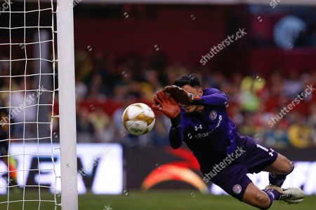 Toluca's Alfredo Talavera dives to stop an attempt to score by America, before the ball bounced off the post and out of bounds, during a Mexico soccer league match in Mexico City, . America defeated Toluca 3-2