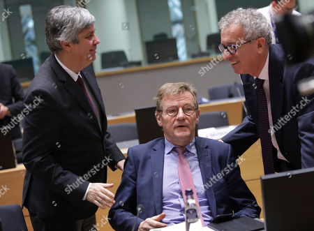Portuguese Economy Minister Mario Centeno, left, and Luxembourg's Finance Minister Pierre Gramegna, right, speak with Belgian Finance Minister Johan Van Overtveldt, center, during a round table meeting of eurogroup finance ministers at the Europa building in Brussels