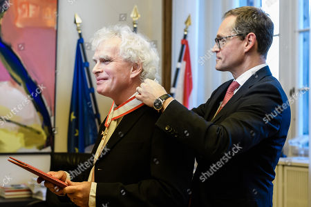 British conductor Sir Simon Rattle (L) receives the Order of Merit of the State of Berlin from Berlin Governing Mayor Michael Mueller (R) in Berlin, Germany, 03 December 2018. Rattle, who became the conductor of the Berlin Philharmonics in 2002, moves on to London and takes over the London Symphony Orchestra.