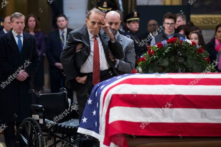 Former US Senate Majority Leader Bob Dole (C) salutes before the casket bearing the remains of former US President George H.W. Bush in the Rotunda of the US Capitol in Washington, DC, USA, 04 December 2018. Bush, the 41st President of the United States (1989-1993), died in his Houston, Texas, USA, home surrounded by family and friends on 30 November 2018.