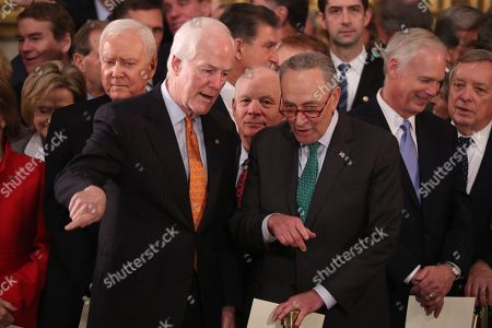 U.S. Senate Majority Whip John Cornyn and Senate Minority Leader Chuck Schumer talk while Senator Orrin Hatch (L-Rear) looks on as they attend ceremonies for the late former U.S. President George H.W. Bush inside the U.S. Capitol rotunda