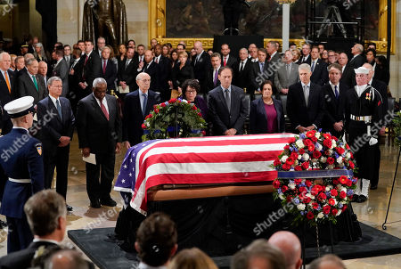 Stock Image of Members of the Supreme Court pause infront of the flag-draped casket of former President George H.W. Bush lying in state at the U.S. Capitol Rotunda, Monday, 3, 2018. From l-r., are Chief Justice John Roberts, Associate Justice Clarence Thomas, Associate Justice Stephen Breyer, Associate Justice Judge Sonia Sotomayor, Associate Justice Samuel Alito, Associate Justice Elena Kagan, Associate Justice Neil Gorsuch, and Associate Justice Brett Kavanaugh