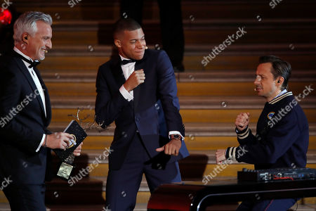 """Stock Picture of Paris St Germain's Kylian Mbappe, center, celebrates with DJ Martin Solveig, right, and David Ginola, right, after receiving the Kopa Trophy during the Golden Ball, """"Ballon d'Or"""" award ceremony at the Grand Palais in Paris, France, Monday, Dec.3, 2018. Awarded every year by France Football magazine since Stanley Matthews won it in 1956, the Ballon d'Or, Golden Ball for the best player of the year will be given to both a woman and a man"""
